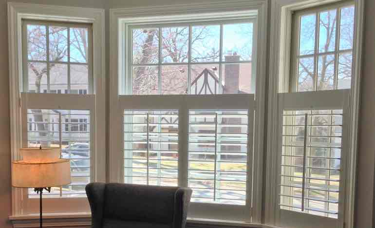 Half-length white shutters in family room bay window.