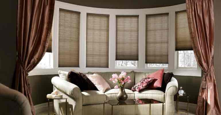 Vertical cellular shades in living room bow window.