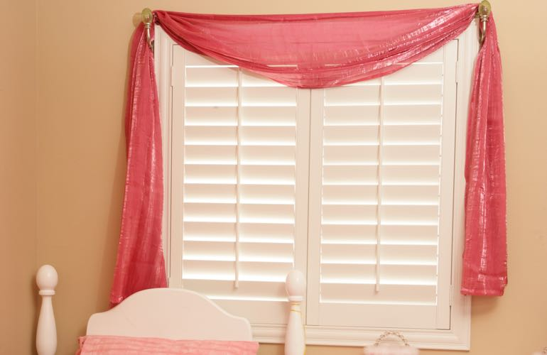 Girl's bedroom with white shutters.