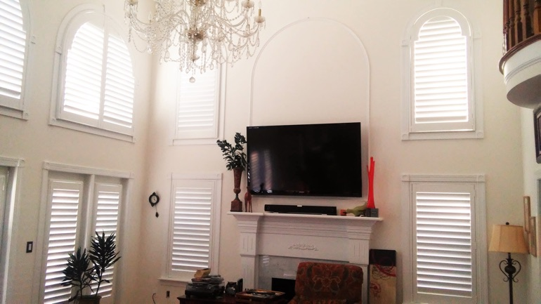 Fort Myers great room with mounted TV and arc windows.