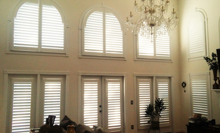 TV room in open concept Fort Myers home with plantation shutters on tall windows.