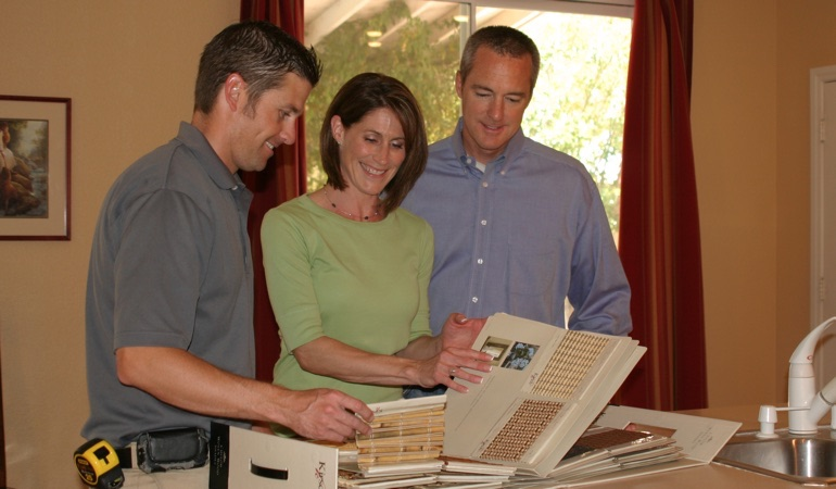 A couple choosing between samples of window treatments.