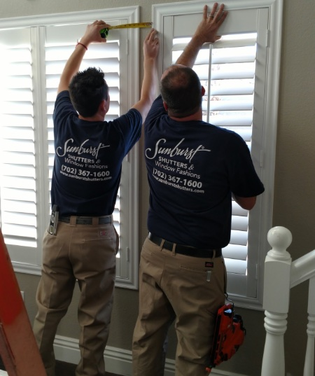 Two Sunburst Shutters technicians installing plantation shutters