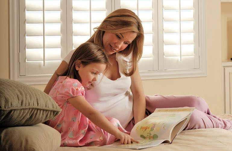 Mother and daughter reading on bed with shuttered windows.