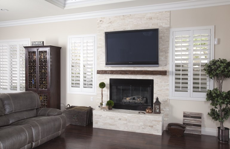 White plantation shutters in a Fort Myers living room with plank hardwood floors.