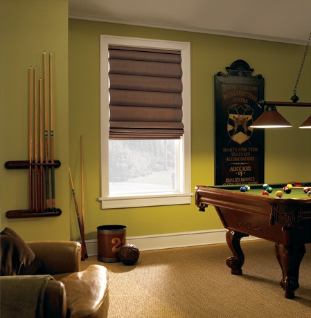 Roman shades in Fort Myers rec room with green walls.