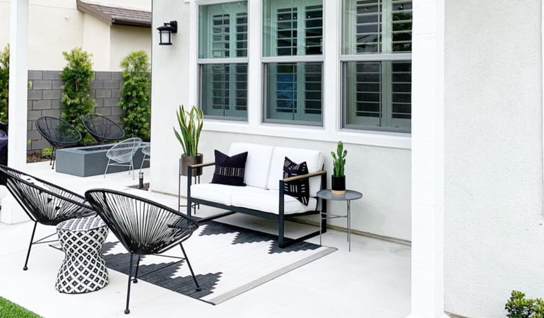 An outside patio with plantation window treatments