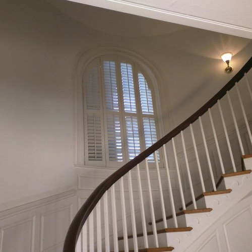 White plantation shutters adorning arched window located in round stairwell.