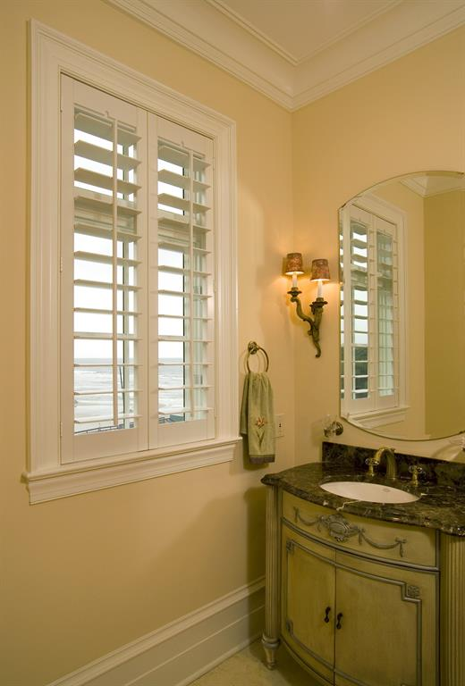 White plantation shutters in a light bathroom looking out over ocean