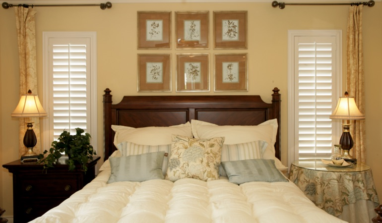 Beige bedroom with white plantation shutters covering windows in Fort Myers