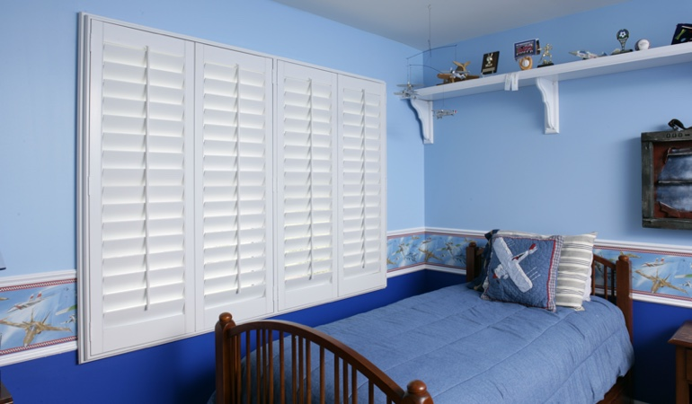 White plantation shutters in blue kids bedroom in Fort Myers